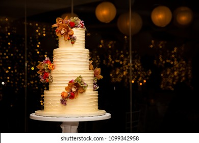 Beautiful white four tier cake with fresh flowers  with fairly light and lanterns glowing in the background.