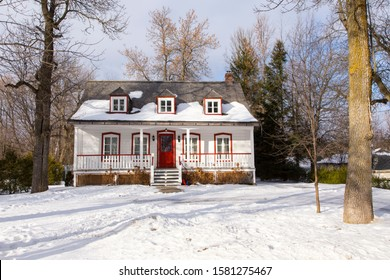 Beautiful white french-style ancestral clapboard house with red trimmed windows and door and grey shingled roof seen during winter, Ste. Foy area, Quebec City, Quebec, Canada
