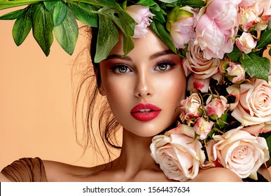 Photo of Beautiful white girl with flowers. Stunning brunette girl with big bouquet flowers of roses. Closeup face of young beautiful woman with a healthy clean skin. Pretty woman with bright makeup