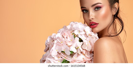 Beautiful white girl with flowers. Stunning brunette girl with big bouquet  of hydrangeas. Closeup face of young beautiful woman with a healthy clean skin. Pretty woman with bright makeup