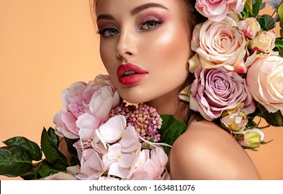 Beautiful white girl with flowers. Stunning brunette girl with big bouquet flowers of roses. Closeup face of young beautiful woman with a healthy clean skin. Pretty woman with bright makeup