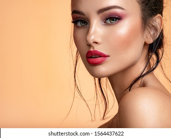 Beautiful white girl with red lips looks to the camera. Stunning brunette girl. Closeup face of young beautiful woman with a healthy clean skin. Pretty woman with bright  makeup of eyes.