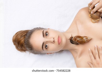 Beautiful white girl with a serious face and brown-haired woman with two snails on the body on a white background