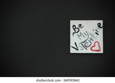 Beautiful white handmade jewellery square shape on black background, be my valentine text