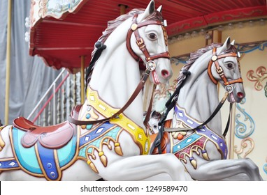 Beautiful white horses Christmas carousel in a holiday park. Two horses on a traditional fairground vintage Paris carousel. Merry-go-round with horses.