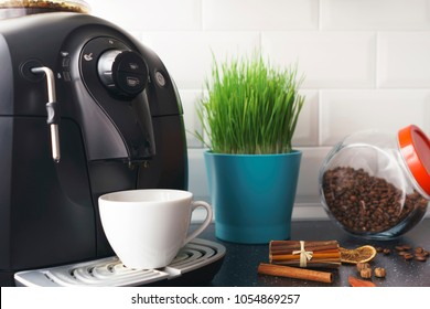 Beautiful white kitchen in an apartment with a coffee machine, a white cup, spices, a glass jar with coffee beans and a green flower in a blue pot. Black surface of the kitchen table