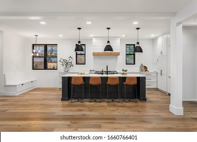 Beautiful white kitchen with dark accents in new modern farmhouse style luxury home