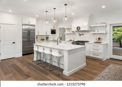 beautiful white kitchen in new luxury home with island, pendant lights, hardwood floors, and stainless steel appliances