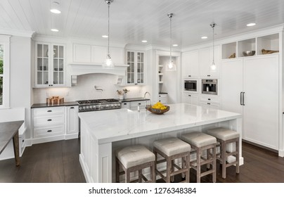 Beautiful White Kitchen in New Luxury Home. Features Hardwood Floors, Island with Sink, and Built-In Refrigerator. Lights are on.