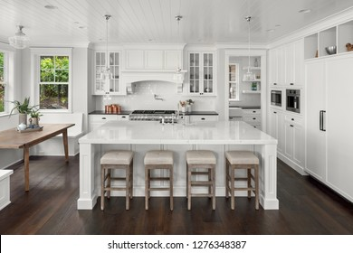 Beautiful White Kitchen in New Luxury Home. Features Hardwood Floors, Eating Nook, Island with Sink, and Built-In Refrigerator.