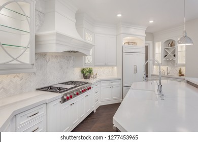 Beautiful White Kitchen in New Luxury Home with White Cabinets, Island, and Counter Top