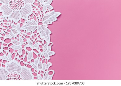 Beautiful white lace cloth on pink background, close up. Copy space. Text place. White lace floral textile fashion pattern. Openwork fabric white lace texture