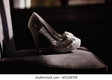 beautiful white lace wedding shoes chair with the back in the dark of the sun close-up