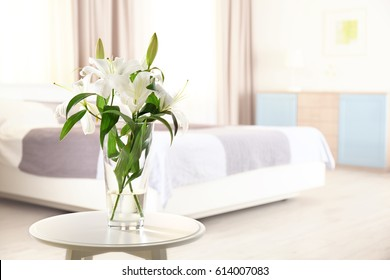 Beautiful white lilies in vase on stool