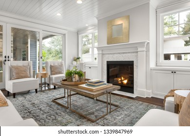 Beautiful white living room in new luxury home with white interior. Has fire in fireplace