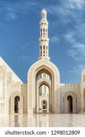 Beautiful white marble arches and minaret in courtyard of the Sultan Qaboos Grand Mosque in Muscat, Oman. Islamic architecture. The Muslim place is a popular tourist attraction of the Middle East.