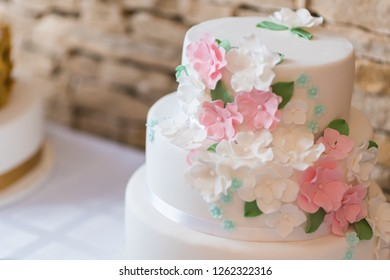 Beautiful white marzipan wedding cake decorated with white and pink spring flowers