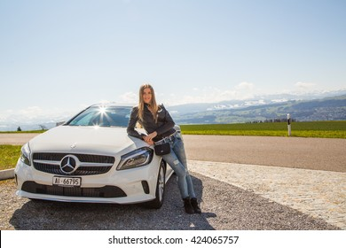 Beautiful white Mercedes parked on the side of the road. Pretty girl standing next to the car.