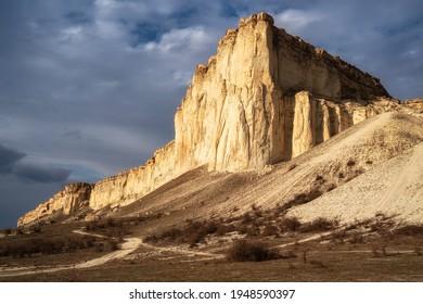 Schöner weißer Berg Gipfel beleuchtet von der Sonne. Weiße Wolken und blauer Himmel auf dem Hintergrund. Epische Felsformation