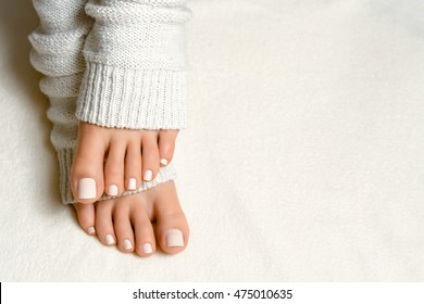 Beautiful white pedicure. Feet in soft knit socks on the plaid
