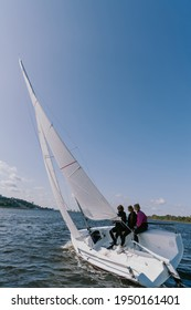 A beautiful white racing single-masted yacht is sailing against a beautiful river landscape with a blue sky. A man and two girls are on board.