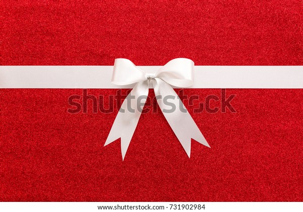 Beautiful white ribbon with bow on colorful red glitter paper or gift box background, top view