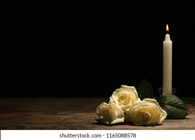 Beautiful white roses and candle on table against black background. Funeral symbol