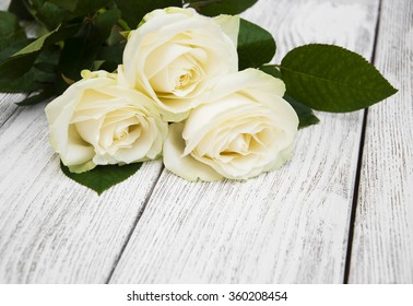 Beautiful white roses on a wooden background