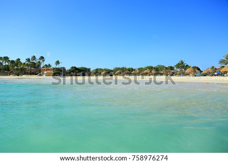 Beautiful white sand beach of Aruba island. Turquoise sea water and green trees. Nature background