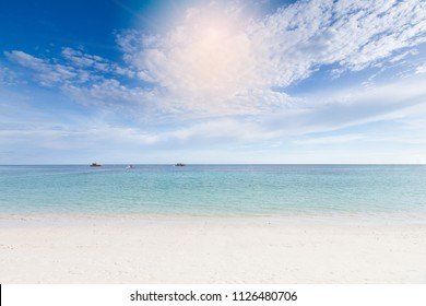 Beautiful white sand beach and cloudy blue sky background.
