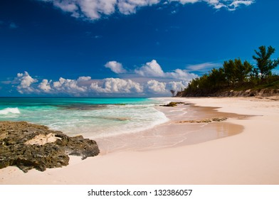 Beautiful white sand beach and turquoise waters and pretty blue sky.  islands of the bahamas.