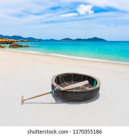 Beautiful white sand beach. Vietnamese round boat on a foreground. Beautiful landscape of Vietnam