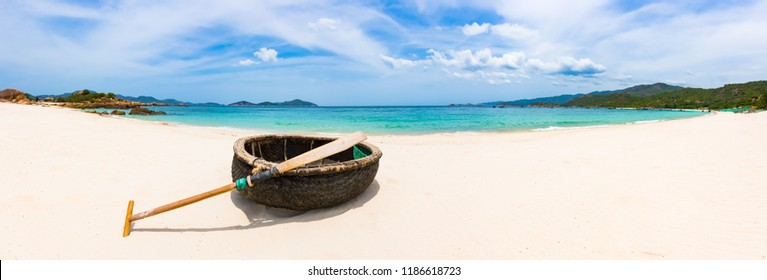 Beautiful white sand beach. Vietnamese round boat on a foreground. Beautiful landscape of Vietnam. Panorama