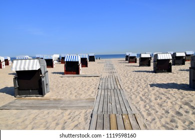 Beautiful white sand beach with wooden boardwalk with clear blue sky and dark blue ocean with many beach chair huts at Warnemunde Germany