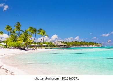 Beautiful white sandy beach in Cap Cana, Dominican Republic. Vacation holidays background wallpaper. View of nice tropical beach with green palms around.