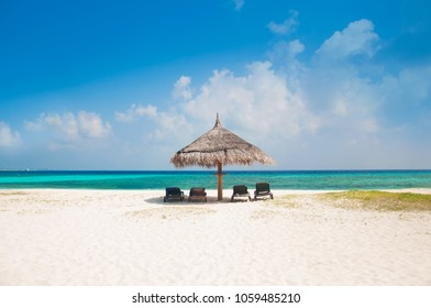 Beautiful white send beach tropical island blue lagoon with two lounge chairs and sun umbrella. Perfect vacation relax sea view on Maldive