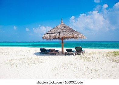 Beautiful white send beach tropical island blue lagoon with lounge chairs and sun umbrella. Perfect vacation relax sea view on Maldive
