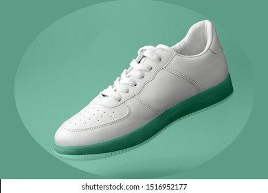 beautiful white sports sneakers with mint colored soles levitate on a mint background