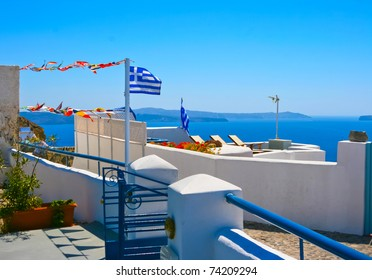 Beautiful white terrace at resort on island of Santorini in Oia, Greece. Traditional greek architecture and national flag of Greece. Aegean sea in a background.