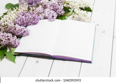 Beautiful white and violet lilac flowers with opened note-book lying on the white wooden background, mock up perspective view