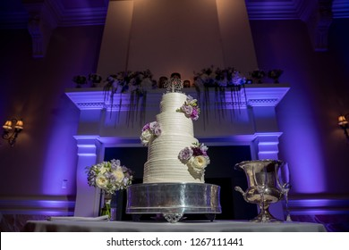 Beautiful white wedding cake with flower accents in front of mantel with purple uplights