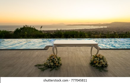 Beautiful white wedding celebration table with floreal decoration in front of a luxurious infinity pool on a wide outdoor terrace facing the city of Naples, Italy and its bay at sunset time