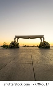 Beautiful white wedding celebration table with floreal decoration on a wide outdoor terrace with wooden exterior floor in the city of Naples, Italy at sunset time