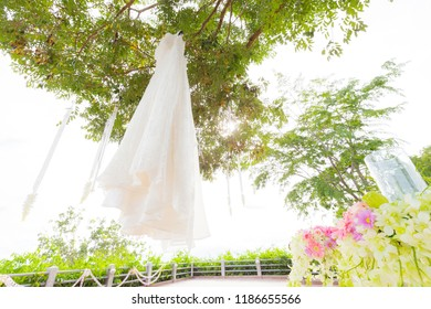 Beautiful white wedding dress hanging on a tree in blooming garden, bride dress for wedding ceremony, selective focus, vintage toned, copy space