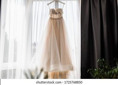 A beautiful white wedding dress. Wedding dress hanging on the window. Backlight.
