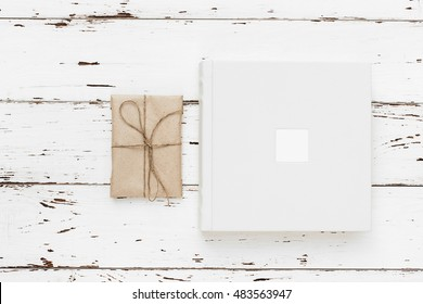 Beautiful white wedding photobook and Vintage handmade gift with cord on rustic  wooden table background. Wedding concept