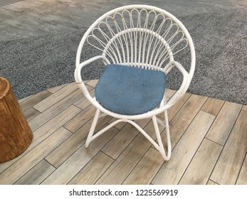 Beautiful white wicker lounge chair with light blue pillow and wooden flooring including modern carpet in background