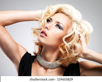 Beautiful white woman with curly  hairstyle posing at studio