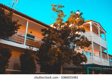beautiful white and wooden hotel building with warm colored tree in the frontside
