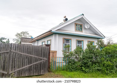 Beautiful white wooden house behind fence with decorative tin furnace accessories over chimney  against cloudy sky background. Solvychegods, Arkhangelsky region, Russia.